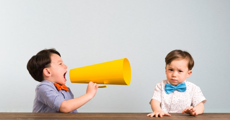 Child is shouting through megaphone to another child